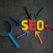 Colourful graphic with SEO letters surrounded by coloured arrows and magnifying glass