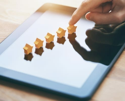 Finger touching 5 stars lined up on a tablet