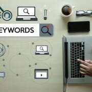 Graphic layout of SEO keywords with man searching on laptop computer