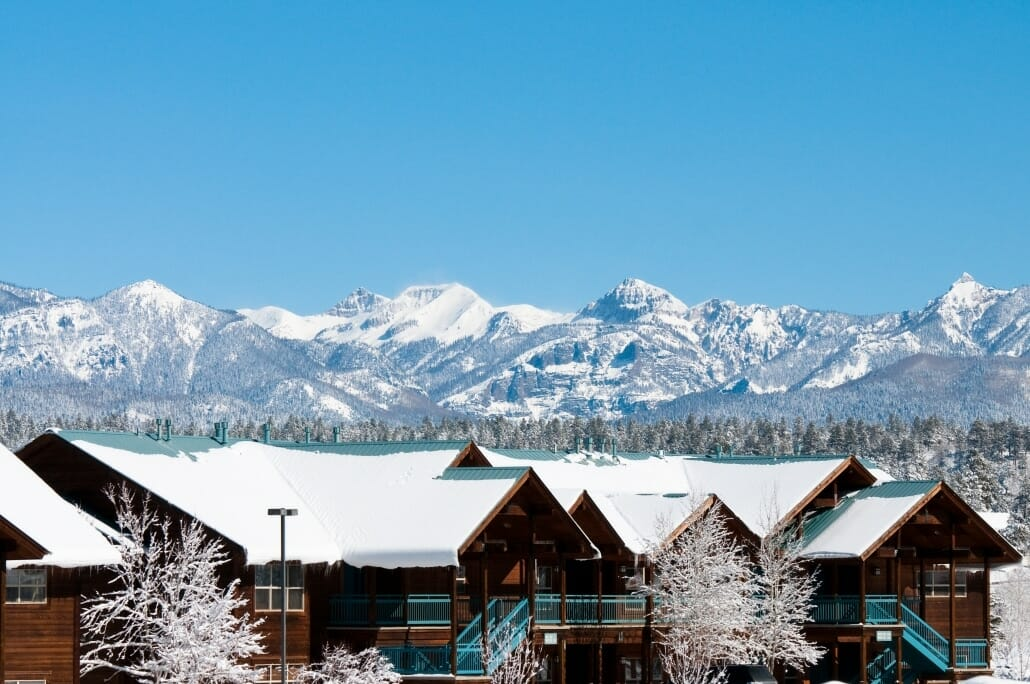 Whistler type townhomes with snow covered trees and mountains in the background