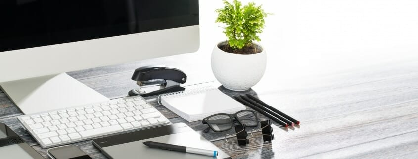 Tidy desk with computer, tablet, cell phone, glasses, pen, pencils, and notepad