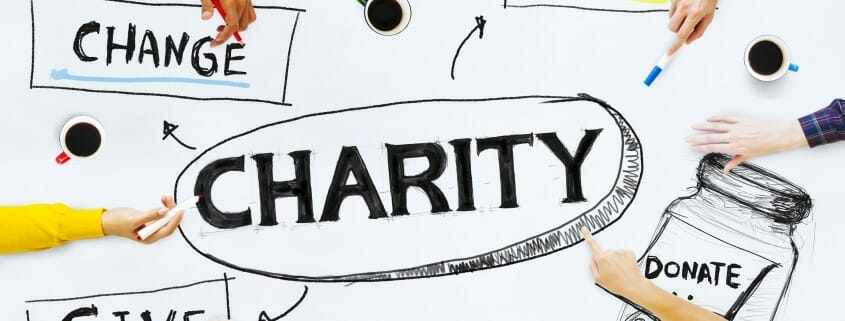 Hands of 8 people brainstorming about Charity - drawing the words CHANGE, HELP, GIVE, DONATE