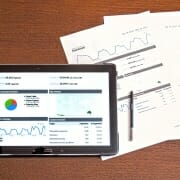 Tablet displaying pie charts and graphs next to 2 sheets of paper with charts printed on them