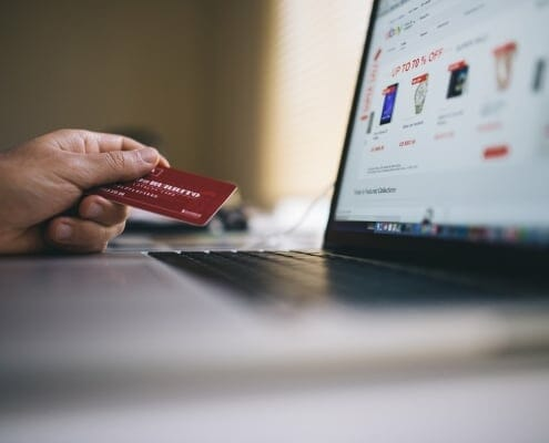 Male hand holding a credit card with a shopping site displayed on a laptop