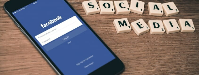 "Cell phone showing Facebook Login page next to ""Social Media"" spelled out using Scrabble pieces"